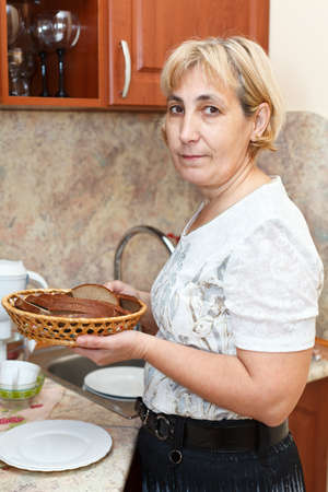 Mature woman standing in kitchen and holding plate with slices of bread photo