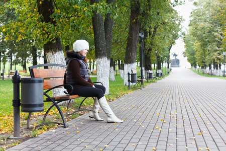 Young beautiful woman sitting alone on a park bench Stock Photo - 11057062