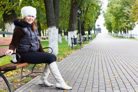 Young beautiful woman sitting alone on a park bench photo