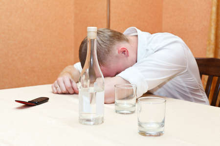 Drunken man laying on table with bottle of vodka and glasses of alcohol. Sleeping guy in white shirt Stock Photo