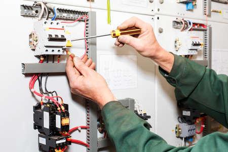 Électricien `s les mains travaillent avec un tournevis dans les câbles et les fils. Banque d'images