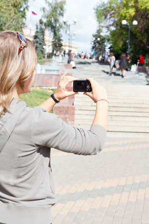 Young beautiful woman photographing city photo