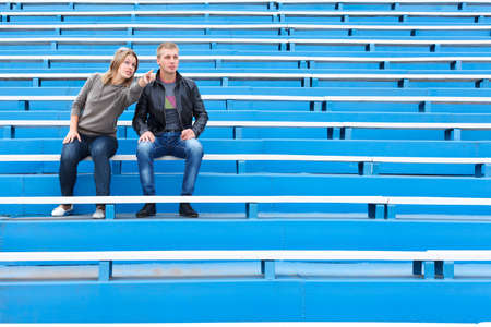 grandstand: Man and woman sitting together on empty sports tribune along Stock Photo