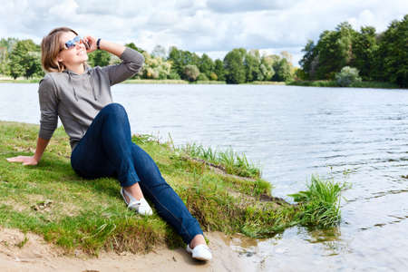 Young woman with sunglasses sitting on the shore of river and talking on the cellphone