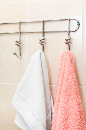 Two terry towels hanging on a hook in the bathroom photo