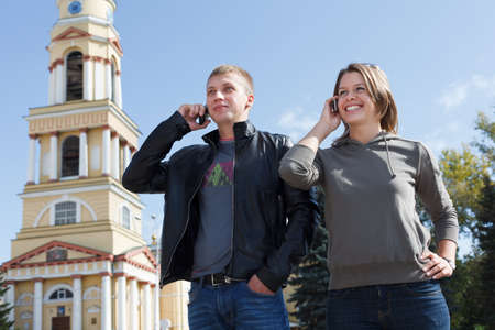2 persons only: Young couple man and woman speaking on mobile phone at the same time Stock Photo