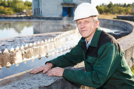 Mature man manual worker in white hardhat near sewage treatment basin