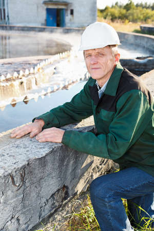 treatment plant: Mature man manual worker in white hardhat near sewage treatment basin