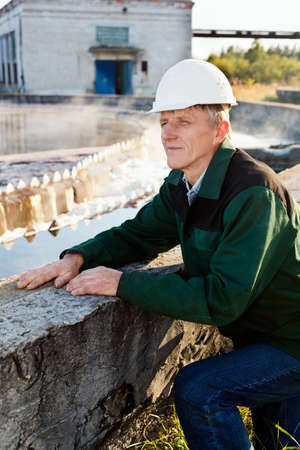 Mature man manual worker in white hardhat near sewage treatment basin photo