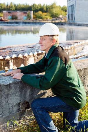 Mature man manual worker in white hardhat near sewage treatment basin photo