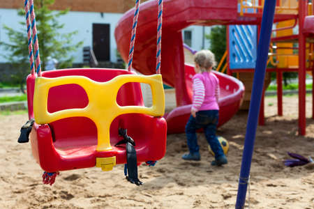 Swing and little child playing in children playground photo
