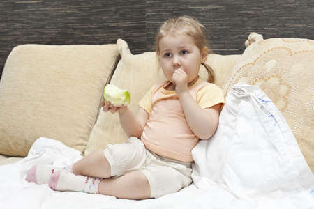 Little child a girl sitting on sofa in domestic room and eating an apple photo