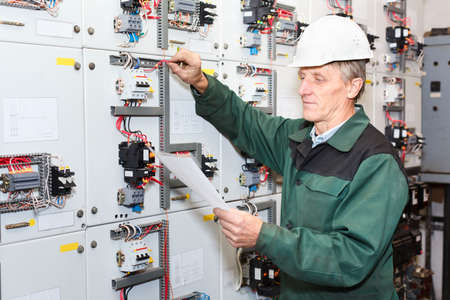 Mature electrician working in white hard hat with cables and wires. Russian people in Russia.  免版税图像
