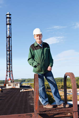 Mature man manual worker in white hardhat in roof against industrial chimney Stock Photo - 11392706