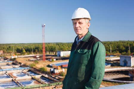 Mature man manual worker in white hardhat near sewage treatment basin Stock Photo - 11392697