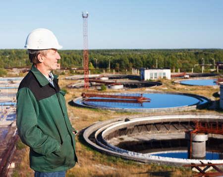 aguas residuales: Hombre maduro trabajador manual en el casco blanco cerca de tratamiento de aguas residuales cuenca Foto de archivo