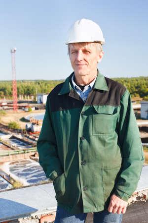 Mature man manual worker in white hardhat near sewage treatment basin Stock Photo - 11392686