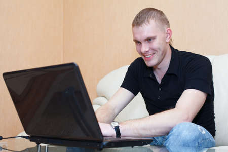 comp: Handsome man playing in games on laptop. Male sits in domestic room interior