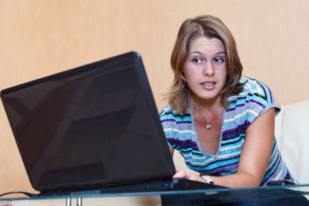 comp: Young woman playing in games on laptop. Girl sits in domestic room interior