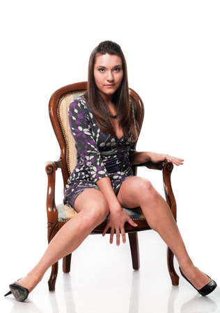 Beautiful white woman in dress on armchair. Long hair. Studio shot. White background photo