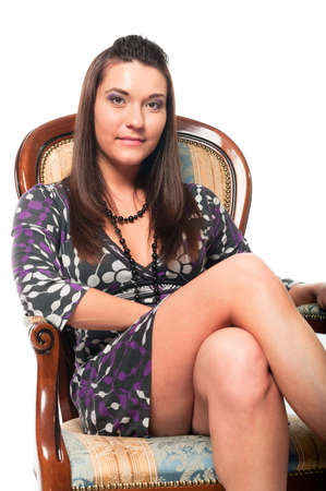 Beautiful white woman in dress on armchair. Long hair. Studio shot. White background photo