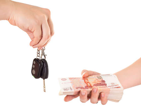 Car key in hand and cash money in other hand isolated ob white background photo