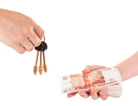 House key in hand and cash money in other hand isolated ob white background photo