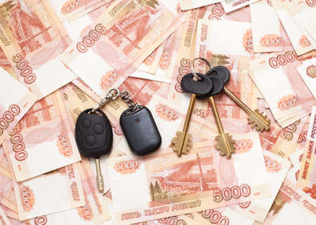 House keys and car key on money cashnotes background photo