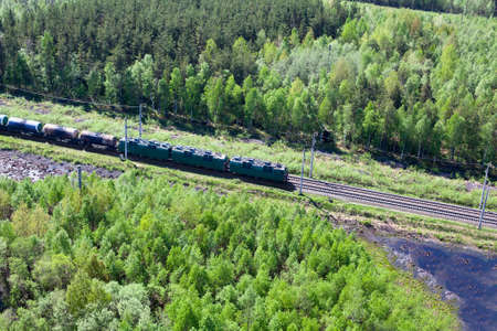Freght train on railway in the middle of evergreen forests photo