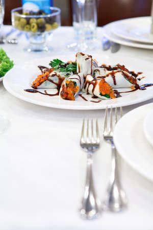 Russian rolled pancakes with red caviar in a plate on the table photo