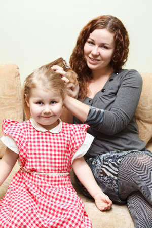 Mother and little daughter sitting on couch. Woman combing daughter hair photo