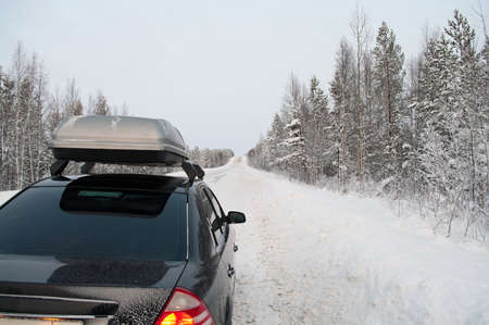 Car trip in winter snowy road in northern forests photo