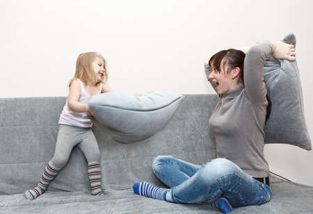 Little child and young mother in pillow fighting on sofa photo