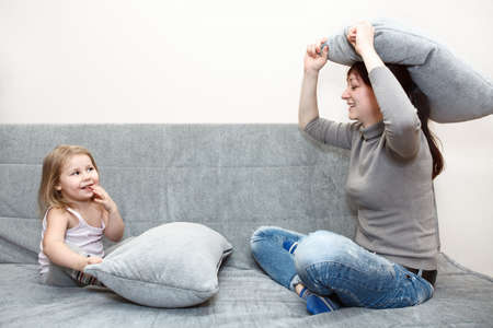 Little child and young mother in pillow fighting on sofa Stock Photo - 11856800