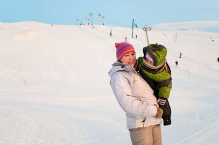 Mother and her little child standing on ski mountain. Cold winter day photo