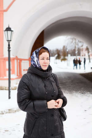Russian woman in winter clothes against Orthodox monastery building. Pilgrimage photo