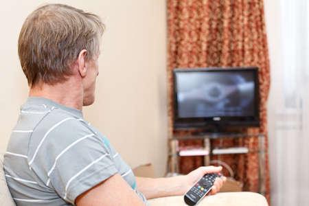 ver tv: Senior hombre con mando a distancia sentado en el sofá y mirando el televisor Foto de archivo
