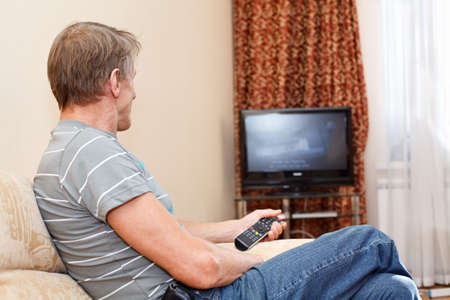 Senior man with remote control sitting on couch and looking at tv set photo