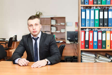 man behind: Handsome male business executive sitting behind a bookstand Stock Photo