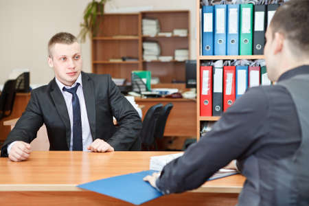 Young business man sitting against at table in office photo