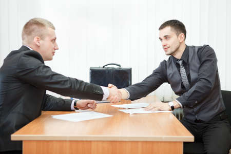 Young business man shaking hands with colleague across the table photo