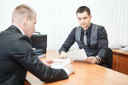 Young business man executives with business documents at work photo