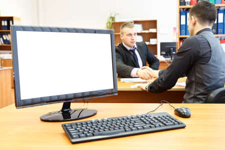businesspersons: Office computer on desk and two businesspersons on background handshaking
