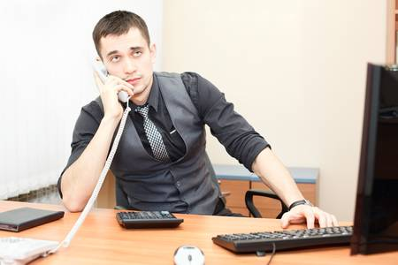 calling: Hombre de negocios inteligente hablar por tel�fono mientras se trabaja en la computadora de escritorio Foto de archivo