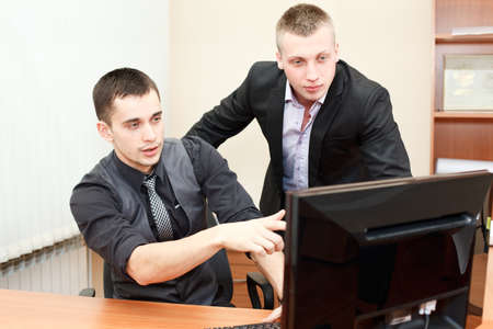 Closeup of young business man pointing at the screen and showing something to his colleague photo