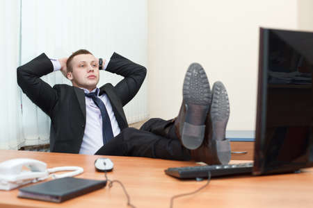 Handsome young business man resting with feet on desk photo