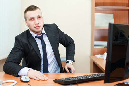 Portrait of a successful young businessman sitting and working a modern office  photo