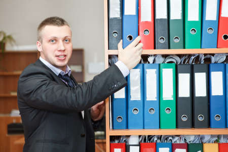 Handsome male business executive standing behind a bookstand photo