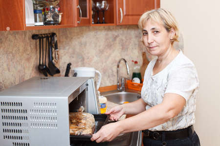 Mature woman standing in kitchen near opened stove photo