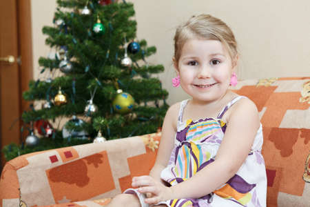 Small smiling girl sitting on couch with a christmas tree behind. photo